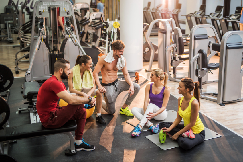 High angle view of five happy people taking a break from exercising in a gym and talking.