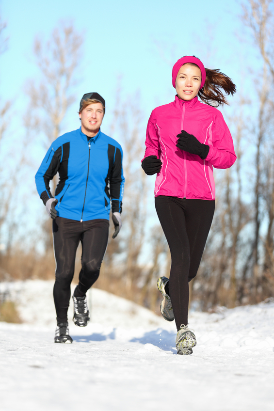 Young couple running dressed warmly in fleeces and gloves jogging in sunshine across winter snow in the countryside.