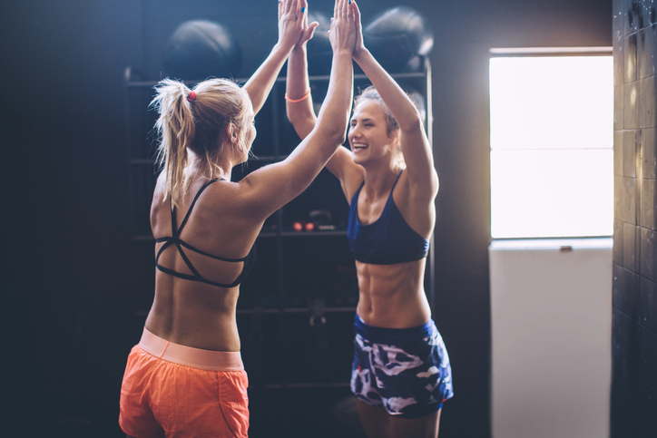 Two girls congratulate each other on well to done training. Professional sportists. Wearing sports clothing.